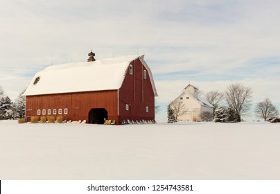 Beautiful snowy winter farm scene of a large red barn and a white corn crib against a color sky. Concepts of rural, farm life, family farm, winter
