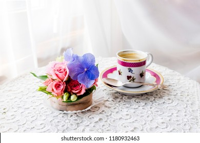 Beautiful soft pink roses and a blue hydrangea in the form of a capcake and a cup of coffee on a table covered with a white cloth. morning light through a white curtain