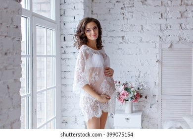 Beautiful soft and sensual pregnant girl in white transparent dress standing near a window in a bright interior home and smiling
