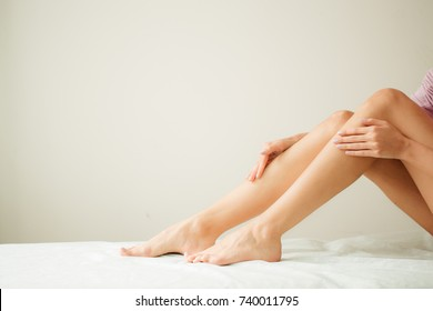 Beautiful Soft Skin. Closeup Of Long Woman Legs With Perfect Hairless Smooth And Silky Skin, Woman's Hand Touhing Her Sexy Slender Leg