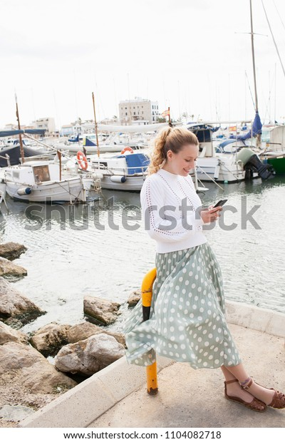 Beautiful solo traveller young woman visiting coastal port destination with boats, using smartphone networking on holiday travel discovery, outdoors. Female tourist with technology, lifestyle.