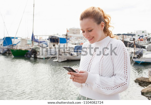 Beautiful solo traveller young woman visiting coastal port destination, using smartphone networking on holiday travel discovery, outdoors. Female tourist with technology, leisure recreation lifestyle.
