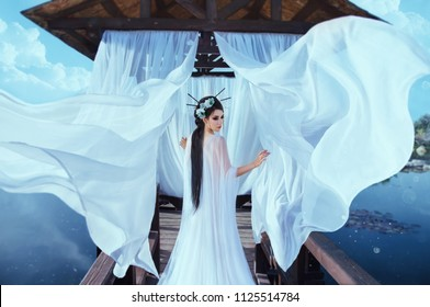 A beautiful sorceress stands on the background of a wooden gazebo by the water, with a white air dress. In the picture there are many flying curtains and silk fabrics. Japanese hairstyle