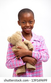 beautiful south african happy friendly smiling teenage black girl with pink flenny pyjamas hugging ragged brown teddy bear
