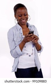 Beautiful South African woman communicating on her cell phone by text message.