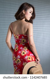 Beautiful South East Asian woman  posing in flower print slinky red dress in a photography studio, isolated on the white background.