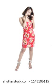 Beautiful South East Asian woman full body posing in flower print slinky red dress in a photography studio, isolated on the white background.