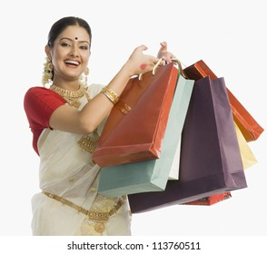 Beautiful South Indian woman holding shopping bags and smiling