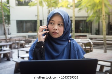 Beautiful southeast asian hijab woman working on laptop and answering phone at outdoors cafea