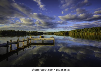 A beautiful southern United States sunset reflecting on a calm lake showing the colors, clouds and far shoreline on the surface. With a wooden dock or pier, mooring balls and a floating trampoline
