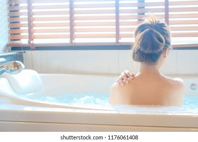Beautiful spa. Back view of a young woman enjoying bathtub in a spa, space for design, Back view, Beauty concept.