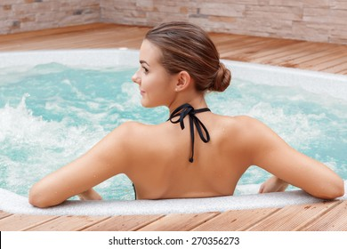 Beautiful spa. Back view of a young woman enjoying Jacuzzi in a spa center