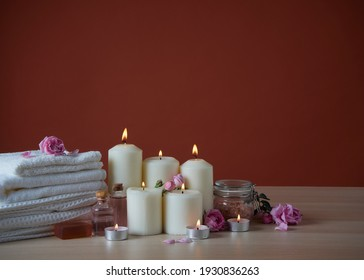 Beautiful spa composition with burning scented candles and aroma oil, pink roses on wooden table