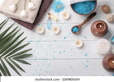 Beautiful spa composition with sea salt, flowers and candles on wooden background, top view