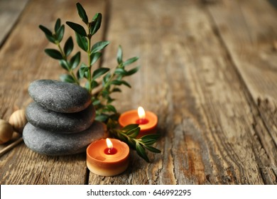 Beautiful spa composition with stones and candles on wooden background