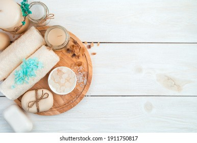 A beautiful spa composition with a towel, candles, flowers and soap on a board on a white background. Top view. The concept of skin cleansing.