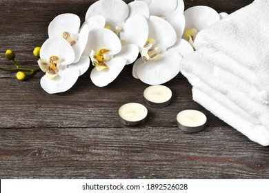 Beautiful spa composition.White towels, orchid flower and candles on a wooden table.