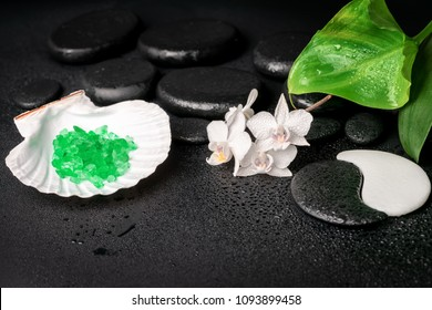 Beautiful spa concept of zen and Yin-Yang stones with drops, white orchid (phalaenopsis), cockshell with sea salt and green leaf