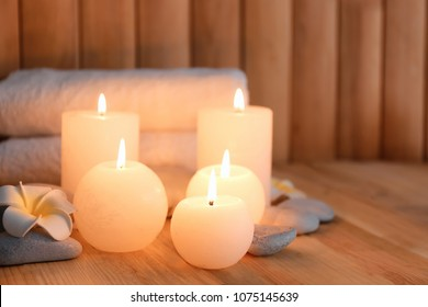 Beautiful spa set with burning candles on wooden background
