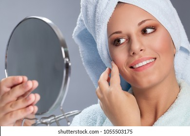 Beautiful spa woman holding mirror and touch her face