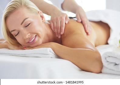 Beautiful spa woman lying on towel in spa salon.