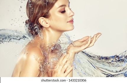 Beautiful spa woman with water splashes. Moisturizing facial skin, beauty and care.