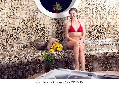 Beautiful spa. Young woman in red bikini enjoying Jacuzzi in a spa center