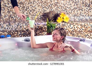 Beautiful spa. Young woman in red bikini drinking fresh juice in a spa center