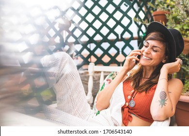 Beautiful Spanish Woman Having a Phone Call at Home. Woman Enjoying her Free Time at Home. Woman in her 30th Sitting on a Deck Chair at Home. Lifestyle Concept.