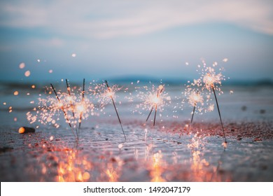Beautiful sparklers on the beach in the sunset light with blurred background.