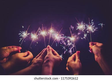 Beautiful sparklers in people hands on black background,holiday and xmas and new year concept.