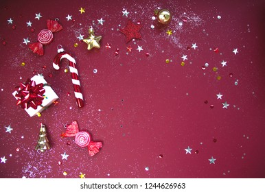 Beautiful sparkling christmas decorative toys, gift box and candies on red background. Flat lay style. Festive concept.