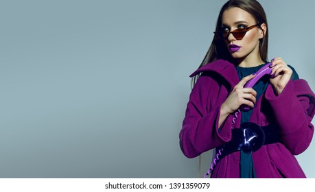 beautiful spectacular long-haired girl in sunglasses and a bright coat holding a lilac phone in hand. Disk phone