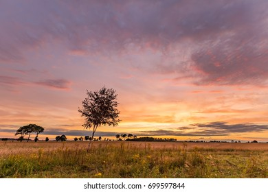 Beautiful spectacular sunset sky over meadows and fields. Sunset sky over landscape.