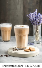 Beautiful speculoos latte with a foam of milk in a glass with coffee grains near it and some cookies. Lavender and another coffee in the back. Dark background
