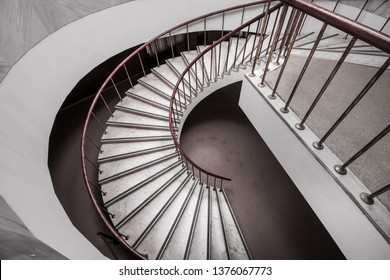 Beautiful spiral white marble staircase with dark red wooden balustrade. Spiral stairway case. Common stone office curved steps. Side view from above.Curved stairs lead down.
