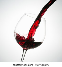 Beautiful splash of red wine in a glass on white background