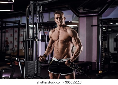 Beautiful sport bodybuilder man on a diet, weight training with dumbbells pumping muscle.With six pack, perfect brakes, shoulders, biceps, triceps and chest.Young adult doing weight lifting at the gym