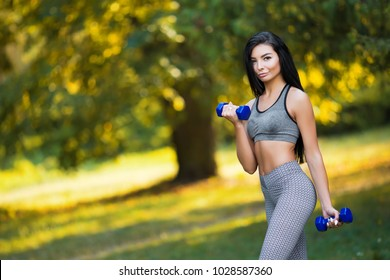 Beautiful sport fitness girl in sportswear doing fitness exercise with dumbbells in the park.