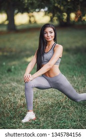 Beautiful sport fitness girl in sportswear doing fitness exercise in the park.