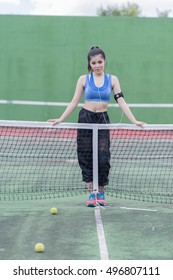 beautiful sport girl drinking water at the tennis court and wearing blue sport bra