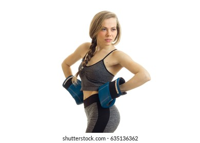 beautiful sport girl in grey suit keeps her hands on the sides in boxing gloves