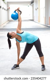 Beautiful sport woman in blue with blue dumb bell demonstrating the windmill pose