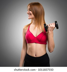 Beautiful sport woman with dumbbells looking lateral on grey background
