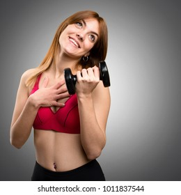 Beautiful sport woman with dumbbells in love on grey background