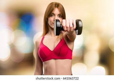 Beautiful sport woman with dumbbells on unfocused background