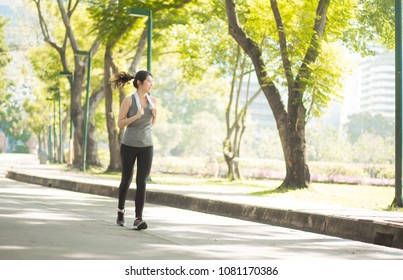 Beautiful Sport woman in sportswear running in the park. Healthy lifestyle and sport concept.