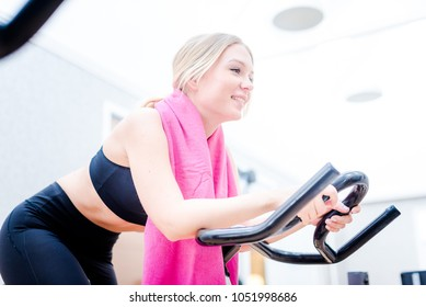 Beautiful sport young woman working out on the exercise bike at the gym, intense cardio workout.