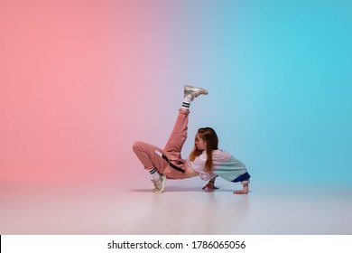 Beautiful sportive girl dancing hip-hop in stylish clothes on colorful gradient background at dance hall in neon light. Youth culture, movement, style and fashion, action. Fashionable bright portrait. - Shutterstock ID 1786065056