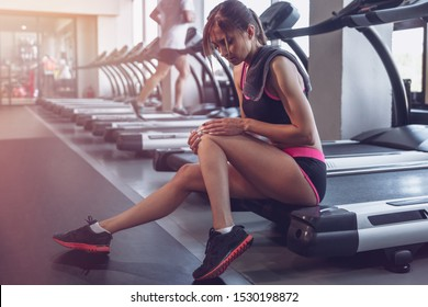 Beautiful sportive girl at gym background, Girl with gray towel in gym, tired after work out, filling pain, injury concept, close up. The girl hurt her leg